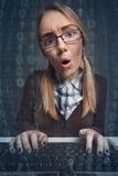 Enttäuschter Frauenhacker, der auf einer Tastatur schreibt Stockfotos
