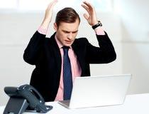 Enttäuschter Geschäftsmann, der Laptop betrachtet Stockbild