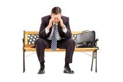 Enttäuschter junger Wirtschaftler, der auf einer Holzbank sitzt Stockbilder