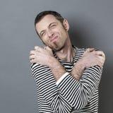 Enttäuschter Mann 40s, der seine Arme auf Schultern für das Ausdrücken des Bedauerns kreuzt Stockfotos