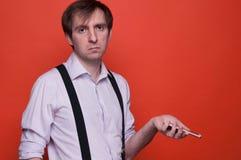 Enttäuschter Smartphone Holding des gut aussehenden Mannes auf orange Hintergrund lizenzfreies stockbild