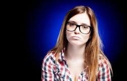 Enttäuschtes und trauriges junges Mädchen mit großen Sonderlingsgläsern Lizenzfreie Stockfotos