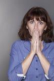 Enttäuschte attraktive reife Frau, die ihren Mund versteckt Lizenzfreie Stockfotos