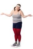Enttäuschte fette Frau auf Skala mit den Armen geöffnet Stockbild
