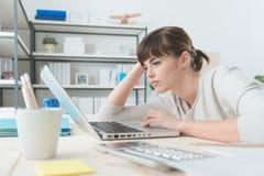 Enttäuschte Frau, die mit einem Laptop arbeitet Stockbild