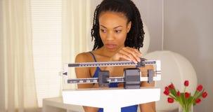 Enttäuschte schwarze Frau überprüft Gewicht Stockfotos