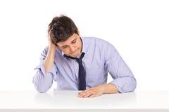 Enttäuschter junger Mann, der auf einer Tabelle sitzt Stockfotos
