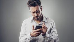 Enttäuschter Mann, der mit seinem Smartphone schreibt Stockbild