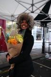 Entusiasmo africano hermoso joven de la demostración de la mujer después de recibir las flores fotografía de archivo