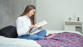 Entusiasta ragazza che legge libro interessante alla camera da letto accogliente a casa stock footage