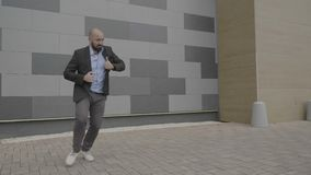 Entusiastisk anställdmankänsla bemyndigade att dansa offentligt nära hans konstnärliga flyttningar för arbetsplatsvisningsalsa - stock video