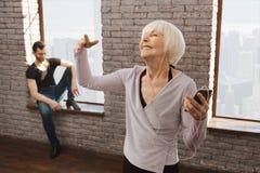 Entusiastisk pensionerad kvinna som tycker om musik under danskursen Arkivbilder