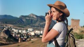 Entusiastisk ung hipsterkvinna som tar fotografibergnaturen genom att använda den yrkesmässiga kameran arkivfilmer
