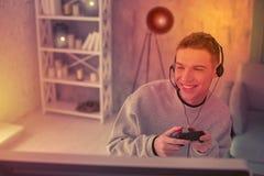 Entusiastisk ung kamrat som använder gamepad för videogame arkivbilder