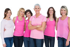 Entusiastiska kvinnor som poserar med rosa blast för bröstcancer Fotografering för Bildbyråer