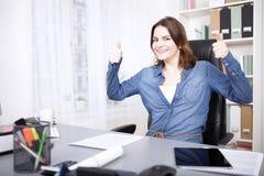Entusiastiskt ge sig för affärskvinna tummar upp Arkivbild