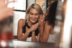 Entuzjastyczna kędzierzawa kobieta szepcze plotki w przyjaciół uszatych fotografia stock