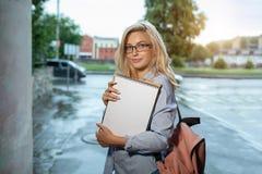 Entuzjastyczna Szczęśliwa piękna młoda dziewczyna uśmiecha się stos książki stoi blisko kampusu l i trzyma obrazy stock