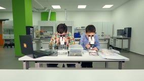 Entuzjastyczne szkolne chłopiec robi nauce eksperymentują w szkolnym laboratorium zbiory wideo