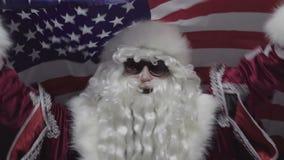 Entuzjastyczny Święty Mikołaj Macha Chorągwianego usa W okularach przeciwsłonecznych zdjęcie wideo