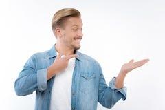 Entuzjastyczny mężczyzna wskazuje przy imaginacyjnym przedmiotem w jego ręce Zdjęcia Royalty Free