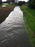 Entwässerungsgraben voll des Regenwassers Stockbild