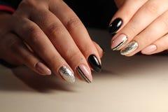 Entwerfen Sie die schwarzen und beige Nägel der Maniküre mit Abstraktion Lizenzfreies Stockbild