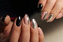 Entwerfen Sie die schwarzen und beige Nägel der Maniküre mit Abstraktion Stockfotografie