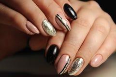 Entwerfen Sie die schwarzen und beige Nägel der Maniküre mit Abstraktion Lizenzfreie Stockbilder