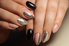Entwerfen Sie die schwarzen und beige Nägel der Maniküre mit Abstraktion Stockbild