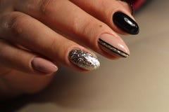 Entwerfen Sie die schwarzen und beige Nägel der Maniküre mit Abstraktion Lizenzfreie Stockfotos