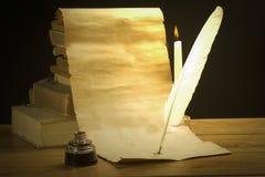 Entwickeltes Pergament, Stift, Buch und Kerze Stockfotos