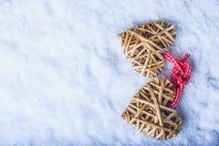 Entwirrte schöne Weinlese zwei die beige flaxen Herzen, die zusammen mit einem Band auf weißem Schnee gebunden wurden Liebe und S Stockfoto