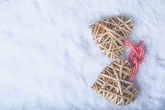 Entwirrte schöne Weinlese zwei die beige flaxen Herzen, die zusammen mit einem Band auf weißem Schnee gebunden wurden Liebe und S Lizenzfreies Stockbild