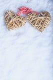 Entwirrte schöne Weinlese zwei die beige flaxen Herzen, die zusammen mit einem Band auf weißem Schnee gebunden wurden Liebe und S Stockfotografie