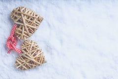 Entwirrte schöne Weinlese zwei die beige flaxen Herzen, die zusammen mit einem Band auf weißem Schnee gebunden wurden Liebe und S Lizenzfreies Stockfoto