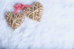 Entwirrte schöne Weinlese zwei die beige flaxen Herzen, die zusammen mit einem Band auf weißem Schnee gebunden wurden Liebe und S Stockfotos