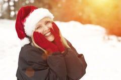 Entzückende blonde Frau, die Santa Hat Outdoors im Schnee trägt Stockfoto