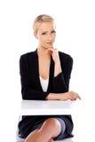 Entzückende blonde Geschäftsfrau, die am Schreibtisch sitzt Stockfotografie
