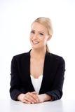 Entzückende blonde Geschäftsfrau, die am Schreibtisch sitzt Stockfotos