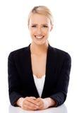Entzückende blonde Geschäftsfrau, die am Schreibtisch sitzt Lizenzfreie Stockfotos