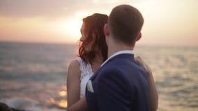 Entzückende Braut und hübscher Bräutigam umarmen zart nahe dem Meer am Hintergrund des hellen bunten Sonnenuntergangs stock video