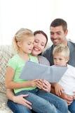 Entzückende Familie, die zusammen ein Buch liest Lizenzfreie Stockfotos