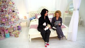 Entzückende Freundinnen haben Spaß und benutzen die Tablette und sitzen auf Bett im hellen Schlafzimmer mit festlichem Weihnachts stock footage