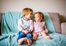Entzückende Geschwister sitzen auf Couch zusammen lizenzfreie stockfotografie