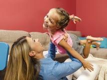 Entzückende glückliche Fliegenwurfsluft des kleinen Mädchens in ihren Müttern bewaffnet lizenzfreie stockfotografie