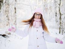 Entzückende glückliche junge blonde Dame im rosa Strickmützeschal, der schlendernden Wald des verschneiten Winters des Spaßes in  Lizenzfreie Stockfotografie