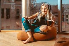 Entzückende junge blonde Frau, die Musik in den Kopfhörern hört Lizenzfreies Stockfoto