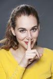 Entzückende junge Frau, die bittet, für Diskretion auf stille Art zu halten lizenzfreies stockbild