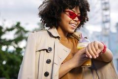 Entzückende junge Frau, die Zeit überprüft und Saftschale hält Lizenzfreie Stockbilder